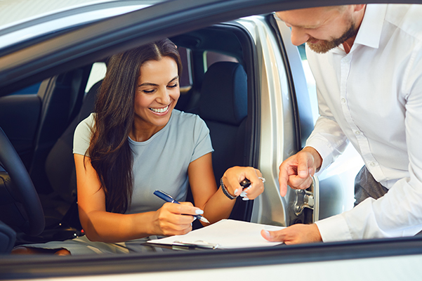 A young woman buys a car in a car showroom.