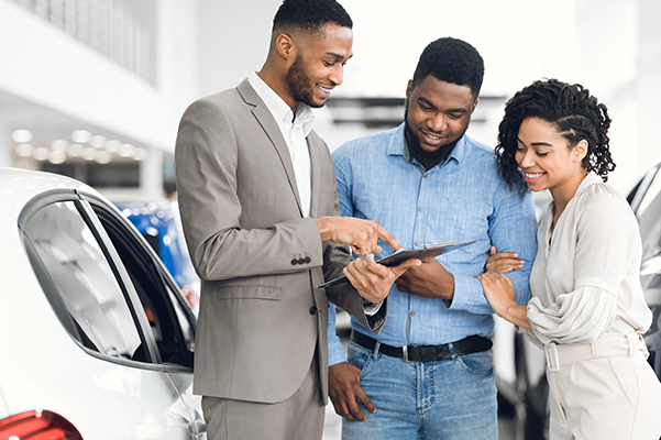 Salesman Offering Couple A Car Standing In Auto Rental Office