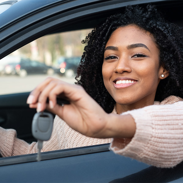 Lady holding car keys out of the car window